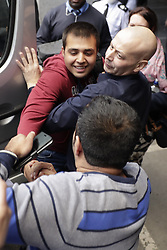 © Licensed to London News Pictures. 17/10/2016. Croydon, UK. Afghani refugee Haris is held back by an immigration official as he tries to reach out to his uncle Jan Ghazi (below) as he leaves the Home Office immigration centre in Croydon. British authorities are bringing over about 100 children this week to be reunited with their relatives. The French government have announced that they will be dismantling the camp this month. credit: Peter Macdiarmid/LNP