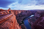 A photographer takes pictures overlooking the Colorado River at Horseshoe Bend, Page, Arizona.