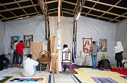 © Licensed to London News Pictures. 30/08/2015. Calais, France. Christian worshippers pray at the Sunday mass in the Ethiopian Orthodox church in the centre of the refugee camp in Calais, also known as the Jungle. Tomorrow the French PM, Manuel Valls, will visit the day centre Jules Ferry at the camp. Photo credit : Isabel Infantes/LNP