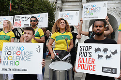 A group of demonstrators from Amnesty International protest declaring 'Say no to police violence in Rio', with a band of Samba drummers at Marble Arch in London.