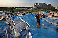 Solar panels provided by SELCO are seen on the roof top of Mosidul Haque's shop in ramshackle settlement near Herbal flyover in Bangalore, India on Dec 22, 2015. Haque runs SELCO's pay-s-you-go-style electricity charging business from his shop. (Photo by Kuni Takahashi)