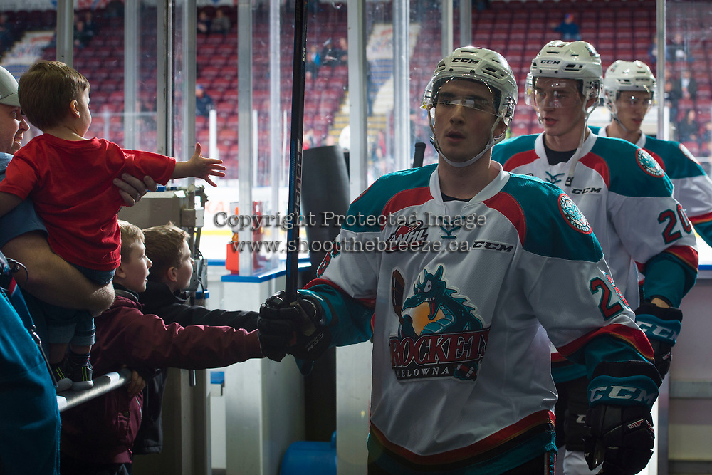 KELOWNA, CANADA - FEBRUARY 24: Liam Kindree #26 of the Kelowna Rockets high fives a young fan as he exits the ice after warm up against the Kamloops Blazers  on February 24, 2018 at Prospera Place in Kelowna, British Columbia, Canada.  (Photo by Marissa Baecker/Shoot the Breeze)  *** Local Caption ***