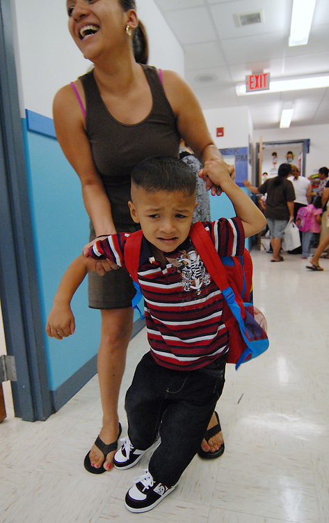Three-year-old Jose Medina Jr. struggles with his mother Maria Hernandez as she takes him into Brenda Pizano's PreKinder at Travis Elementary School on Monday.