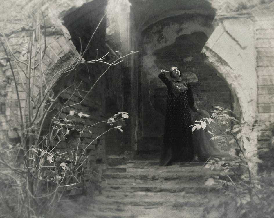 A woman in a vintage gown, holding a veil, standing among old ruins.