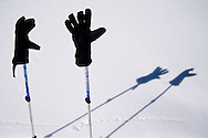 A graphic design of shadows created by gloves and ski poles on snow.