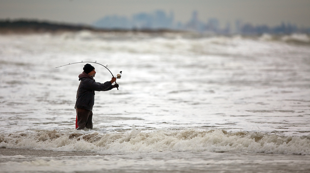A fisherman working the shoreline at Sandy Hook NJ during a powerful coastal storm (nor'easter) pummeled the coastline.   The fall fishing run of striped bass and bluefish is legendary at the park.