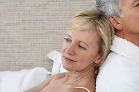 Middle-aged couple sitting back to back in bedroom close-up