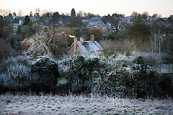 © Licensed to London News Pictures. Frost covered trees and rooftops at sunrise over Buford in Oxfordshire on December 29, 2014 as most of the UK woke to freezing temperatures.. Photo credit : Ben Cawthra/LNP