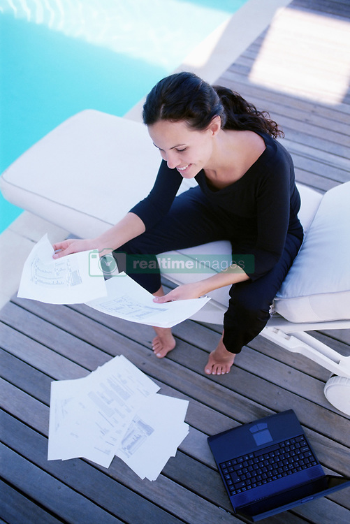 Dec. 14, 2012 - Woman working by the pool (Credit Image: © Image Source/ZUMAPRESS.com)