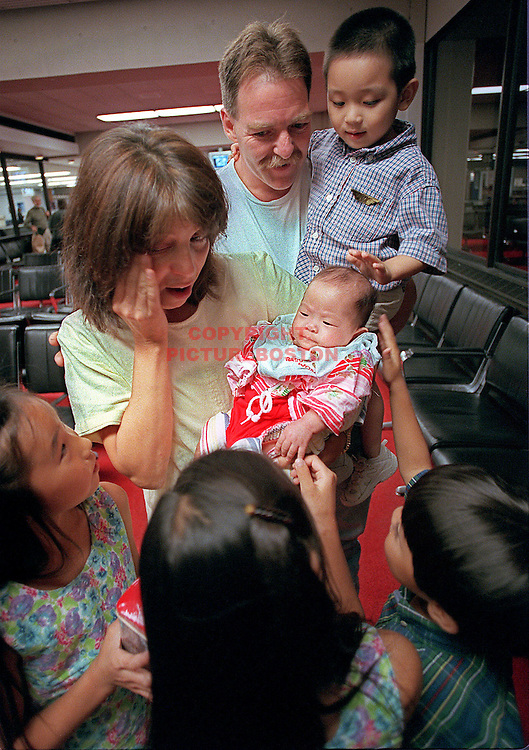 "Joe and karen Aucoin welcome their 7th child (5th Korean adopted baby) ""Hadley (4mths old) at Logan airport... children Sam , Noah,Tess and Taylor (clockwise from top) Staff Photo: Mark Garfinkel"