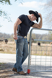 rugged cowboy in a black tee shirt and cowboy hat leaning on a ranch gate
