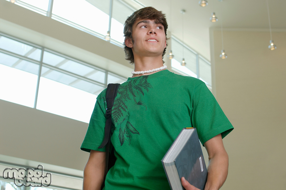 Male student holding book in university
