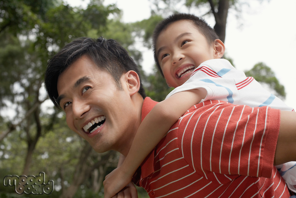 Father giving son piggyback (7-9) in park