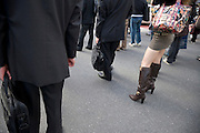 legs of a fashionably dressed young woman surrounded by  traditional corporate dressed businessmen