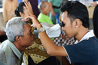 Staff of Bali Eye assessing a patient for problems with his sight, Bali, Indonesia.