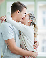 Loving couple kissing while hugging in house