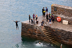 © Licensed to London News Pictures. 04/08/2018. St Austell, UK. Children jump off Gorran Haven quay in Cornwall during hot weather. Photo credit : Tom Nicholson/LNP