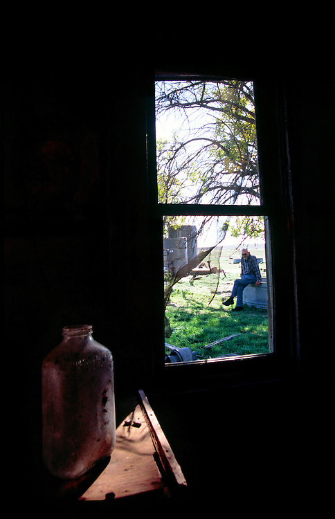 An old farmer, who grew up in the area,  reflects in the farmyard of a vacant homestead in eastern Colorado