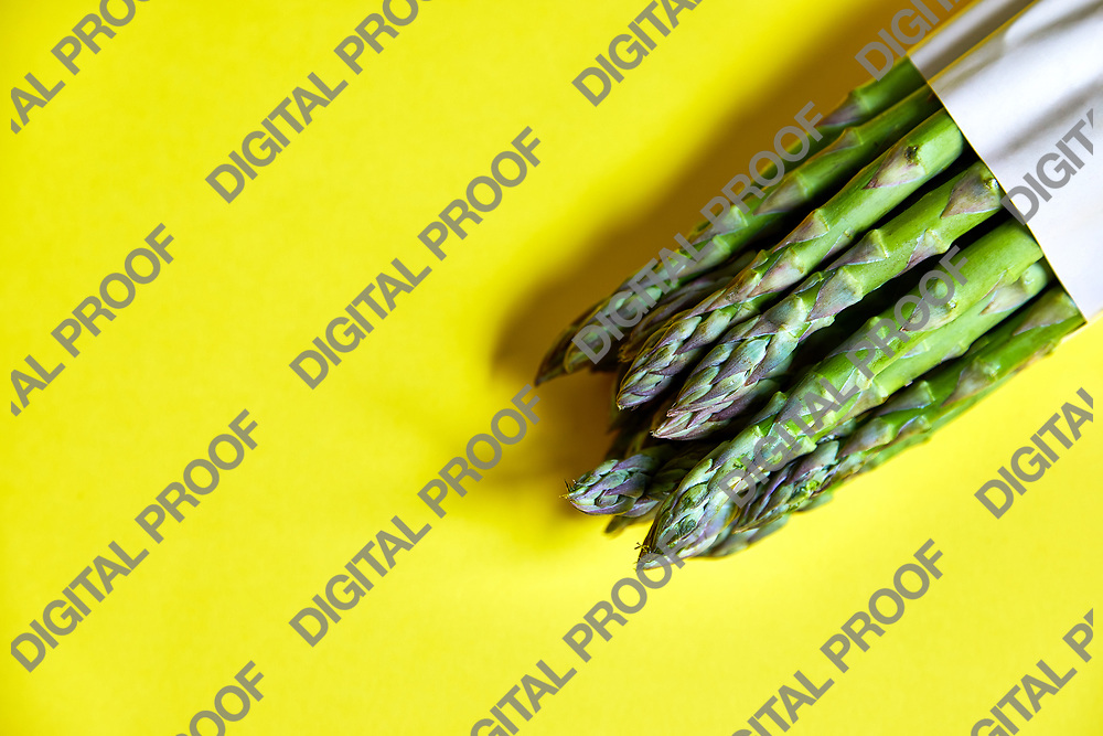 bunch of fresh and healthy asparagus tied with paper with yellow background