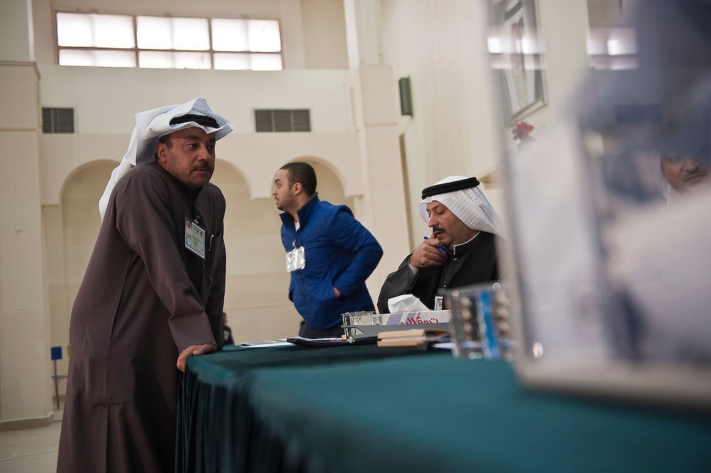 Candidates' representatives watch the vote at a polling station in Kuwait City during the February 2 parliamentary elections. A total of 400,296 Kuwaiti men and women are eligible to vote to choose from among some 285 candidates, including more than 20 women candidates, for a new 50-seat parliament.