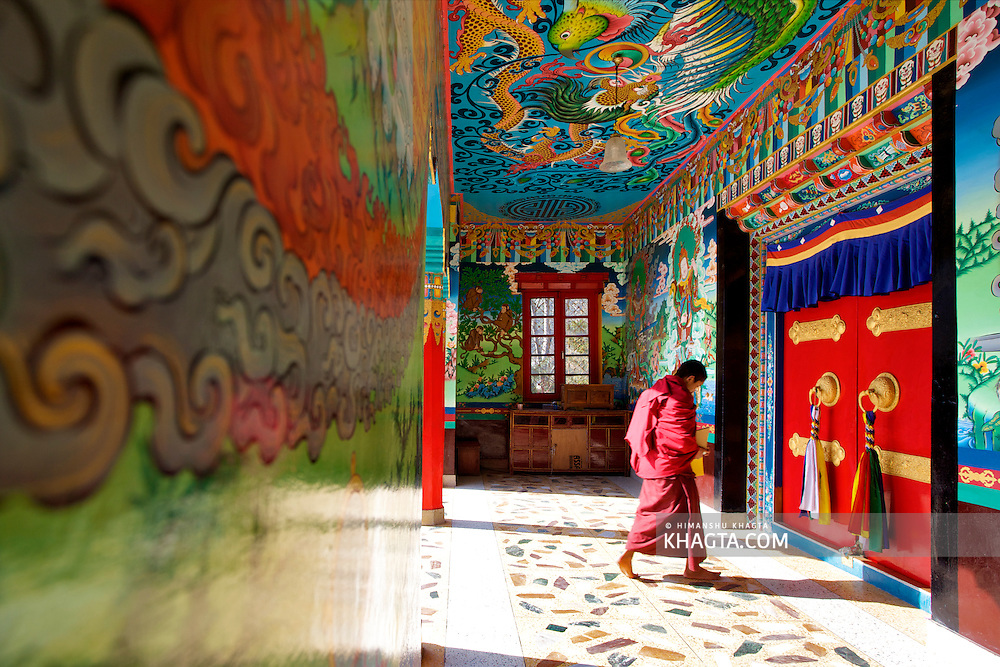 A monks walks through the colorful walls of a Gompa, to open its door for the daily prayers in Rewalsar, Mandi, Himachal Pradesh, India
