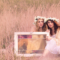 Two young women sitting together in the sun with an old window wearing white summer dresses with head garlands made from white daisiy flowers