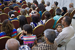 © Licensed to London News Pictures. 27/07/2014. Hamdaniyah, Iraq. 5 year old Iraqi Christian Mosul refugee Rania Minowar Salim (L) looks up during a service held at a church in Hamdaniyah, Iraq.<br /> <br /> Having taken over Mosul Iraq's second largest city in June 2014, fighter of the Islamic State (formerly known as ISIS) have systematically expelled the cities Christian population. Despite having been present in the city for more than 1600 years, Christians in the city were given just days to either convert to Islam, pay a tax for being Christian or leave; many of those that left were also robbed at gunpoint as they passed through ISIS checkpoints. Photo credit: Matt Cetti-Roberts/LNP