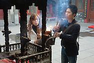 Lighting incense in the Xingguo Monastery on Thousand Buddha Mountain, Qianfo Shan, on the edge of Jinan city, Shandong, China
