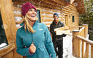 A couple gathers up fire wood during a snow storm to heat up their cabin.