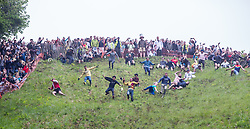 © Licensed to London News Pictures 26/05/2018, brockworth, Gloucester, UK. The annual cheese rolling race held at Coopers Hill, Brockworth outside Gloucester. Competitors race down the extremly steep slippery hill chasing a double Gloucester cheese, the winner of each race recieves the cheese as thier prize. Pictured here :  Local legend Chris Anderson in the yellow jersey leads the field in his second race wher he won his second race of the day to gain his 22nd and all time record breaking win - Photo Credit : Stephen Shepherd/LNP