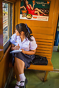 07 JANUARY 2013 - KANCHANABURI, THAILAND: A student doing homework looks out the window in a third class train car on the train between Bangkok (Thonburi station) and Kanchanaburi. Thailand has a very advanced rail system and trains reach all parts of the country.    PHOTO BY JACK KURTZ