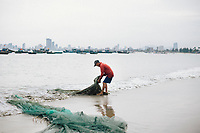 A man pulls in his fishing net with a view of Danang, Vietnam in the background.