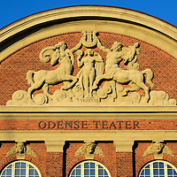 Odense Teater Pediment Reliefs in Odense, Denmark <br /> I was fascinated by the reliefs by Thomas Bærentzen on the arched pediment of the Odense Teater.  The half man, half horse figure is a centaur from Greek mythology.  Far less common is the female version called a centauride.  They are holding a lyre, a harp-like instrument dating back to Greek antiquity.  In the center is a nude statue of Veritas, the Roman goddess of truth.  Flanking this ensemble are elf-like creatures holding theater masks. The theater was established in 1796 and this building opened in 1914.