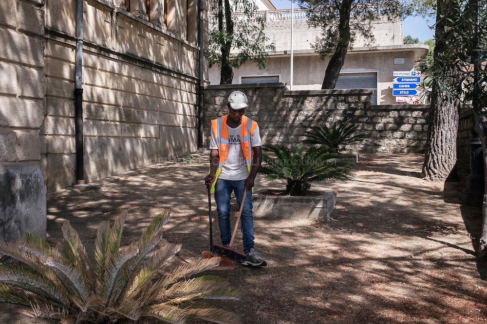 An asylum seeker is cleaning the streets of Riace as results of a Project paid with EU funds.