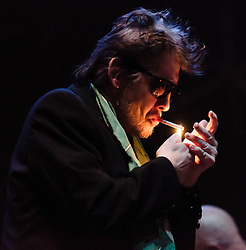 © Licensed to London News Pictures. 20/12/2012. London, UK.   Shane MacGowan of The Pogues lights a cigarette as they perform live at The O2 Arena for their only UK live date of 2012 as part of their 30th Anniversary Tour.  The Pogues are a Celtic punk band from London, formed in 1982 and fronted by Shane MacGowan.  Members include Shane MacGowan (vocals, guitar, banjo, bodhrán),.Spider Stacy (vocals, tin whistle), Jem Finer (banjo, mandola, saxophone, hurdy-gurdy, guitar, vocals), Andrew Ranken (drums, percussion, harmonica, vocals), .James Fearnley (accordion, mandolin, piano, guitar), .Philip Chevron (guitar, vocals),  Darryl Hunt (bass guitar),.Terry Woods (mandolin, cittern, concertina, guitar, vocals).     Photo credit : Richard Isaac/LNP