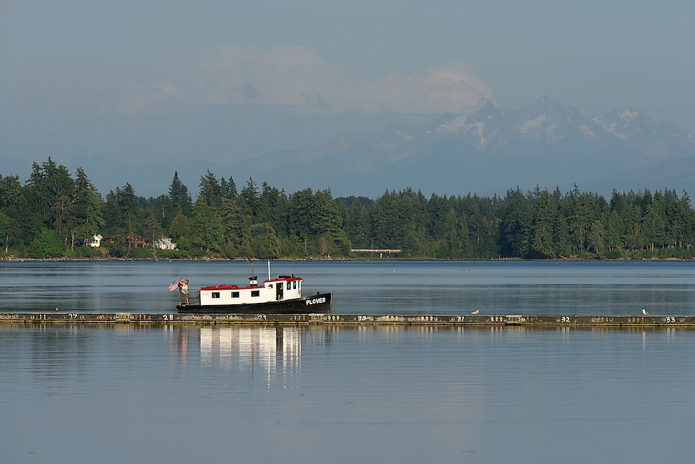 Couple embracing on the Plover with Mount Baker in the distance.  Semiahmoo Bay, Washington State