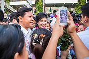 27 FEBRUARY 2013 - BANGKOK, THAILAND: Pol Gen PONGSAPAT PONGCHAREON (left) and YINGLUCK SHINAWATRA, Prime Minister of Thailand, campaign for Pongsapat's election to Governor of Bangkok, while a person photographs Yingluck with a smart phone. Police General Pongsapat Pongcharoen (retired), a former deputy national police chief who also served as secretary-general of the Narcotics Control Board is the Pheu Thai Party candidate in the upcoming Bangkok governor's election. (He resigned from the police force to run for Governor.) Former Prime Minister Thaksin Shinawatra reportedly personally recruited Pongsapat. Most of Thailand's reputable polls have reported that Pongsapat is leading in the race and likely to defeat Sukhumbhand Paribatra, the Thai Democrats' candidate and incumbent. The loss of Bangkok would be a serious blow to the Democrats, whose base is the Bangkok area.     PHOTO BY JACK KURTZ