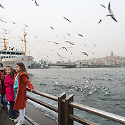 Two small girls pose for photos with the seagulls on the waterfront of Eminonu in Istanbul. In the background is the Galata Tower.