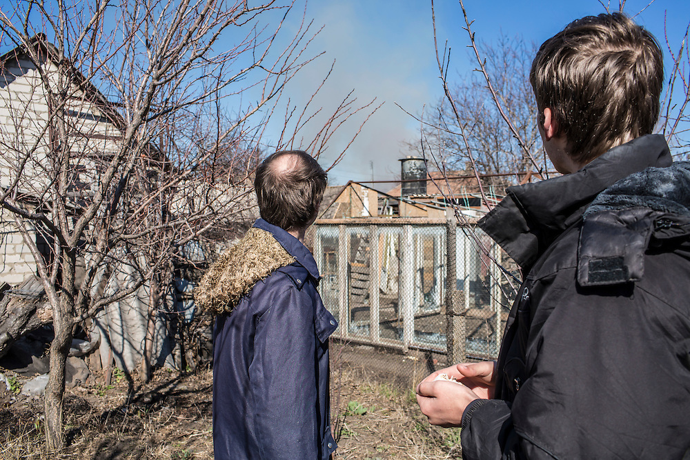 LUHANSK, UKRAINE - MARCH 16, 2015: Aleksandr Kryukov, left, and Pavel Pavlov watch smoke in the distance from the yard of the house where Kryukov lives with his grandmother in Luhansk, Ukraine. The two have created a series of popular YouTube videos involving scientific experiements. CREDIT: Brendan Hoffman for The New York Times