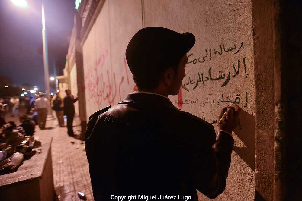 """Cairo, Egypt, Dec. 4, 2012-A young protester takes his time painting graffiti on the walls of the presidential palace, where thousands of demonstrators gathered to oppose President Mohamed Morsi's Nov. 22 decree granting himself near-absolute power. A fractious coalition of liberal, secular, Christian and other non-Islamists groups are fearful that Morsi, who is backed by the Islamist Muslim Brotherhood, is paving the way towards a dictatorship. They have been protesting since his decree, but Tuesday night was the first time since Morsi issued it that they marched to the palace. """"This is another revolution,"""" one protester said, although so far, Morsi has showed no signs of heeding their demands. (Photo by Miguel Juarez Lugo)"""