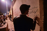 "Cairo, Egypt, Dec. 4, 2012-A young protester takes his time painting graffiti on the walls of the presidential palace, where thousands of demonstrators gathered to oppose President Mohamed Morsi's Nov. 22 decree granting himself near-absolute power. A fractious coalition of liberal, secular, Christian and other non-Islamists groups are fearful that Morsi, who is backed by the Islamist Muslim Brotherhood, is paving the way towards a dictatorship. They have been protesting since his decree, but Tuesday night was the first time since Morsi issued it that they marched to the palace. ""This is another revolution,"" one protester said, although so far, Morsi has showed no signs of heeding their demands. (Photo by Miguel Juarez Lugo)"