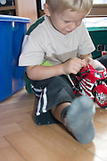 Child age 3 playing with new battery operated wheelie motorcycle. Balucki District Lodz Central Poland