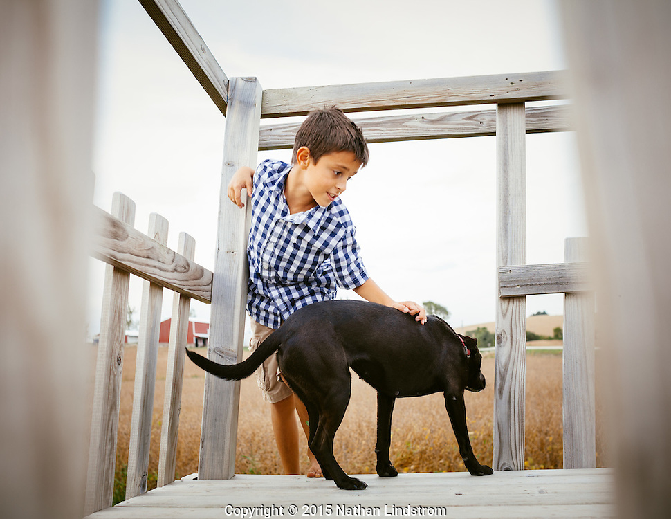 A boy playing with his dog. Various farms in Johnson and Iowa County, Iowa.<br />