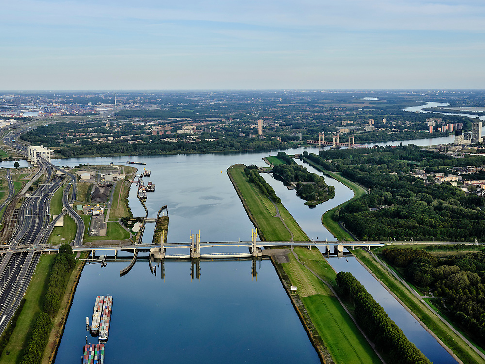 Nederland, Zuid-Holland, Rotterdam, 14-09-2019; Haven van Rotterdam, Botlek, Hartelkanaal met Hartelkering (stormvloedkering) tijdens de jaarlijkse Functioneringssluiting. <br /> De kering, onderdeel van de Deltawerken, vormt samen met de Maeslantkering de Europoortkering en beschermt Rotterdam en achterland bij extreme waterstanden. De keringen worden een maal per jaar, voordat het stormseizoen begint, getest. Tijdens het sluiten van de kering ligt alle scheepvaartverkeer naar de Rotterdamse haven stil. In de achtergrond Botlekbrug en Shell-olieraffinaderij, Hoogvliet.<br /> Aerial view of one of the two storm surge barriers. This barrier, the Hartelkering in the Hartel canal, together with the greater nearby Maeslant barrier (in the New Waterway), are tested during the so-called functioning closure, taking place one a year before the storm season begins. The waterway and canal, leading to the Port of Rotterdam, are closed during the test.<br /> <br /> luchtfoto (toeslag op standard tarieven);<br /> aerial photo (additional fee required);<br /> copyright foto/photo Siebe Swart