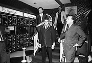 17/07/1967<br /> 07/17/1967<br /> 17 July 1967<br /> Opening of new men's salon at Brown Thomas, Grafton Street, Dublin. Brendan O'Reilly, the TV personality opened a new Mens Department in Brown Thomas and Co. Ltd.. In the new department was a hairdressing salon where while getting your hair done it was possible to make phone calls from the chair. Image shows Mr. Gerry McLoughlin (centre) demonstrating one of the suits that were being made at the shop with Brendan O'Reilly (left) and Mr. John McGuire, Managing Director, Brown Thomas Group.