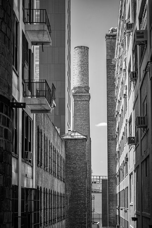 View on a narrow alley between city buildings in black and white.