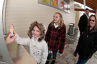 """A cold and wintry day after the storm but Mattison Douville is all smiles as she receives her first """"DQ"""" of the season with some extra sprinkles as her sister Alexis waits her turn along with parents Dan and Tammy Friday afternoon.  (Karen Bobotas/for the Laconia Daily Sun)"""