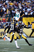 Jacksonville Jaguars rookie wide receiver Keelan Cole (84) leaps in the air to catch a pass while defended by Pittsburgh Steelers cornerback Artie Burns (25) and Pittsburgh Steelers cornerback Joe Haden (21) on a reception good for a gain of 45 yards and a first down at the Steelers 3 yard line in the fourth quarter during the NFL 2018 AFC Divisional playoff football game against the Pittsburgh Steelers, Sunday, Jan. 14, 2018 in Pittsburgh. The Jaguars won the game 45-42. (©Paul Anthony Spinelli)