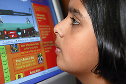 Portrait of girl leaning up to the screen of her computer,