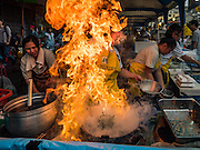 12 OCTOBER 2015 - BANGKOK, THAILAND:  A vendor fries up an order of noodles in a fiery wok on the first day of the Vegetarian Festival in Bangkok's Chinatown. The Vegetarian Festival is celebrated throughout Thailand. It is the Thai version of the The Nine Emperor Gods Festival, a nine-day Taoist celebration beginning on the eve of 9th lunar month of the Chinese calendar. During a period of nine days, those who are participating in the festival dress all in white and abstain from eating meat, poultry, seafood, and dairy products. Vendors and proprietors of restaurants indicate that vegetarian food is for sale by putting a yellow flag out with Thai characters for meatless written on it in red.      PHOTO BY JACK KURTZ